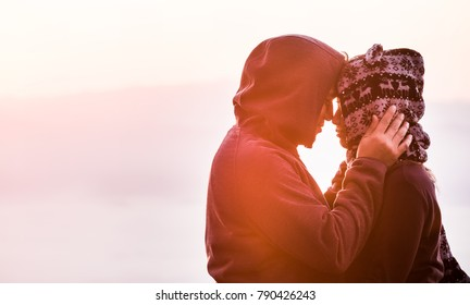 Silhouette of a couple kissing against a sunrise,Silhouette of lovers are kissing in the midst romantic fog over the sunrise,Romantic atmosphere,Valentine's concept,Embrace of a loving couple,Family.
