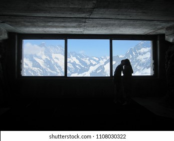 Silhouette of a couple kissing with the mountains of Switzerland through the window behind them.