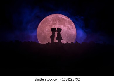 Silhouette of couple kissing under full moon. Guy kiss girl hand on full moon silhouette background. Valentine`s day decor concept. Silhouette of loving couple kissing against the full moon