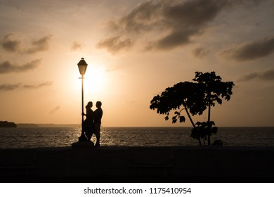 Silhouette of a couple in a lamp over a wall at sunset in Sao Luis do Maranhao