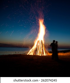 Silhouette of a couple in love against fire background. Romantic evening on the beach