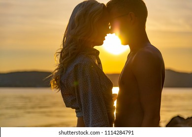 Silhouette of couple in love embracing at the beach against sun