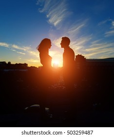 Silhouette of couple in love kissing and touching on the sunset in the city street background.