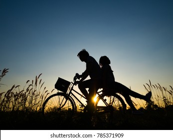 Silhouette of Couple love riding a bike in sunset