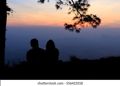 Silhouette of a couple in love sitting and looking view sunset on the mountain.