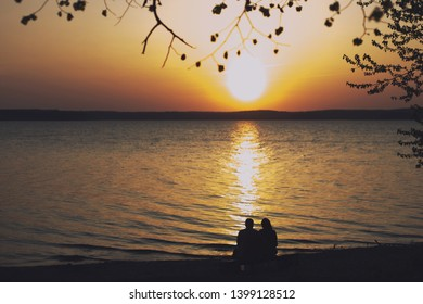 silhouette of a couple in love sitting on a bench on the beach at sunset and hugging