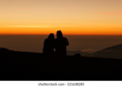 Silhouette couple lovers watching sunrise amoung fog.