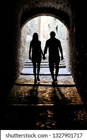 silhouette of couple of man and woman holding hands going through a dark tunnel
