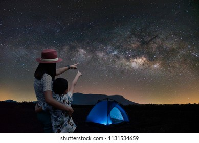 Silhouette couple mother and son Asian standing together. Outdoor camping tent Looking at the stars and the Milky Way in the night. Long exposure, romantic and happy.