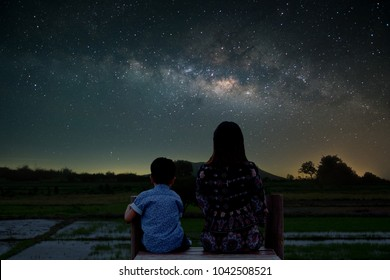 Silhouette Couple Mother and son Sitting at a field view. Enjoy the view of the Milky Way on the romantic night.