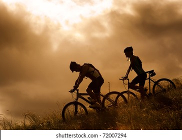 silhouette couple mountainbike riding outdoors at sunset