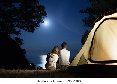 Silhouette of couple near tent looking at moon at night