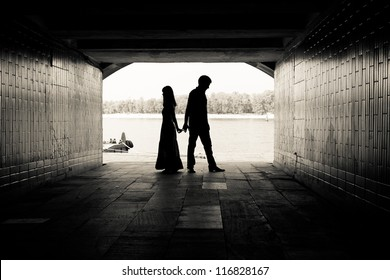 Silhouette of a couple on bright background at the end of an underground pedestrian tunnel