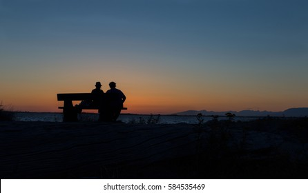 silhouette of a couple on a park bench at the beach watching the sunset