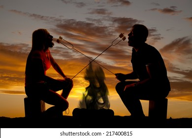 A silhouette of a couple in the outdoors roasting marshmallows over a fire.