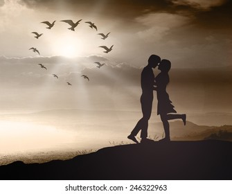 Silhouette couple over blurred sunset background.