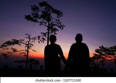 silhouette couple people seeing sunrise on top of mountain