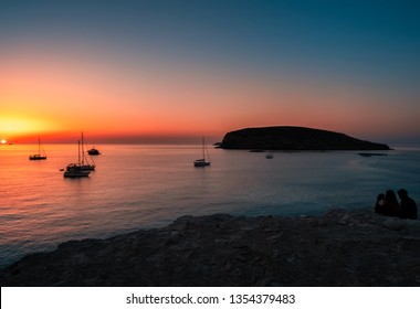 Silhouette of a couple photographing the sunset, of the mediterranean sea, pleasure boats and islet, from the cliff of Cala comte beach in Ibiza, Spain