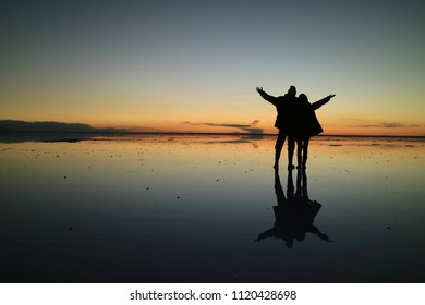 Silhouette of a couple raising their arms for the happy moment on the incredible mirror effect of Uyuni Salt Flats, Bolivia, South America