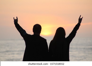 A silhouette of a couple signing devil horns with a blurred background