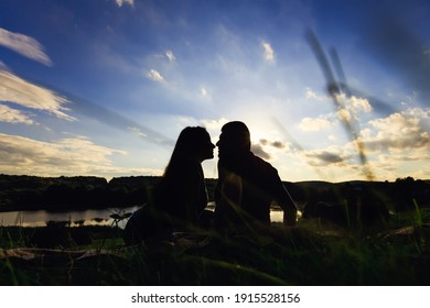 silhouette of a couple sitting kissing on a meadow against the backdrop of a beautiful sunset and nature. Back view.
