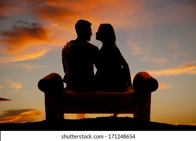 Silhouette of a couple sitting on a bench, outdoors.