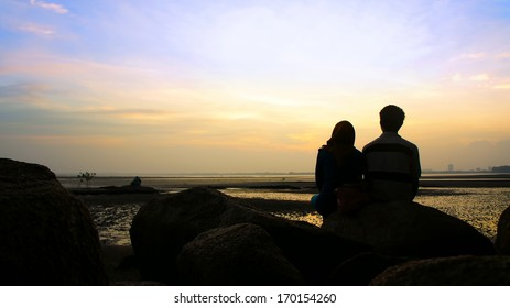 Silhouette of couple sitting on the rock looking at the sun goes down