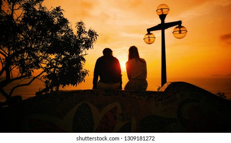 Silhouette of a couple sitting on the tiled wall looking at the sunset