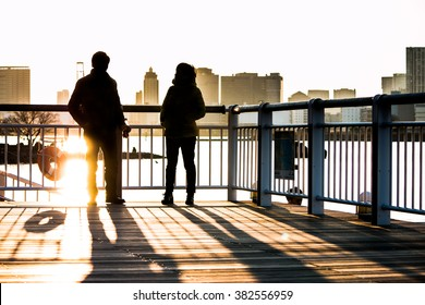 Silhouette of a couple stand on a bridge in the beach at sunset, Odaiba park, Tokyo Japan.