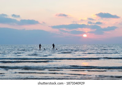 Silhouette couple standing on paddleboards in the ocean at sunset