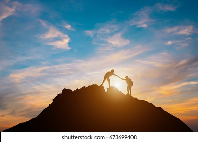 Silhouette of couple teamwork  hiker helping each other on top of mountain