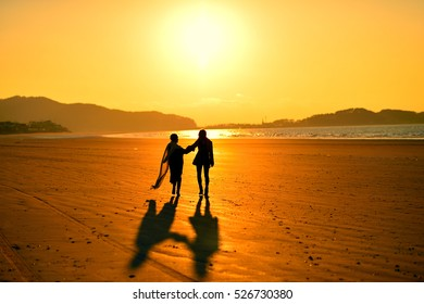 silhouette couple, two friendly couples in the beach at sunset