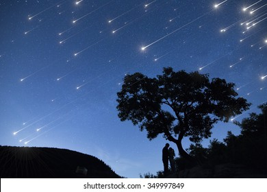 Silhouette couple under a tree and enjoying Star shower  in nights cape