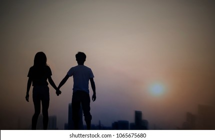 silhouette of a couple walking in a city at dawn or dusk with sky sunset.