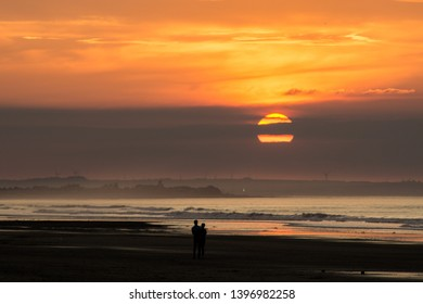 Silhouette of couple walking on a beach at sunset. Saltburn beach, north east coast of England.