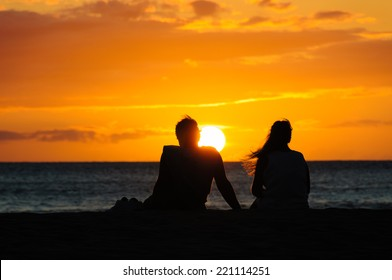 Silhouette of a couple watching a colorful sunset on a beach in Maui, Hawaii, USA