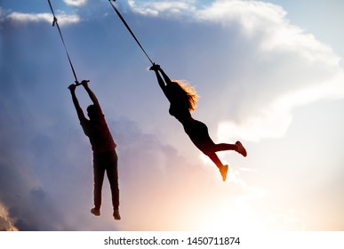 Silhouette of couples. Man and woman silhouette flying in sky. Girl and boy flying on a rope bungee. Humans gymnast hanging on rope against the background of clouds and sunset. Lovers Silhouette.