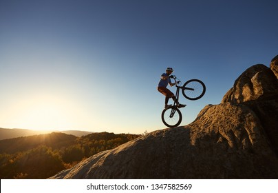 Silhouette of courageous cyclist balancing on back wheel on trial bicycle. Professional sportsman biker making acrobatic stunt on the top of mountain at sunset. Concept of extreme sport. Copy space