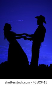 A silhouette of a cowboy dancing with his girl in her dress with the beautiful night sky and mountains behind them.