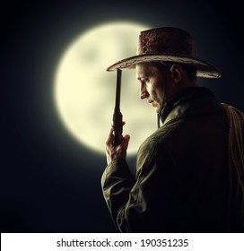 silhouette of cowboy holding hat and revolver outdoor. Full moon