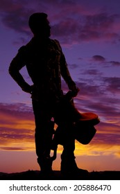 A silhouette of a cowboy holding on to his saddle looking to the side.