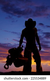a silhouette of a cowboy holding on to his saddle looking down.