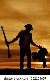 A silhouette of a cowboy holding on to his shotgun and saddle.