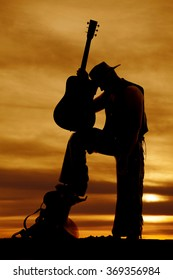 A silhouette of a cowboy holding on his guitar with is head on it.