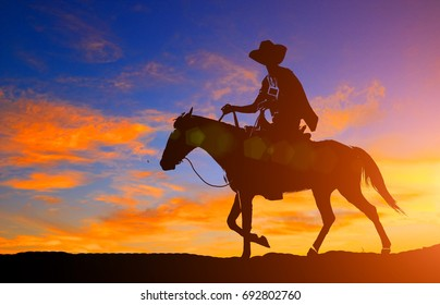 silhouette cowboy and horse on sunset