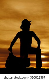 a silhouette of a cowboy kneeling down by his saddle looking to the side.