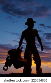 A silhouette of a cowboy looking to the side, holding on to his saddle.