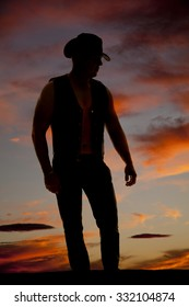 a silhouette of a cowboy in the outdoors, standing and looking down.
