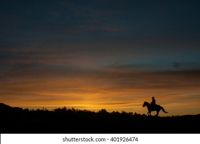 Silhouette of cowboy riding horse at sunset across the horizon