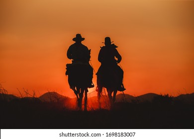 Silhouette the cowboy riding on a mountain with an yellow sky.